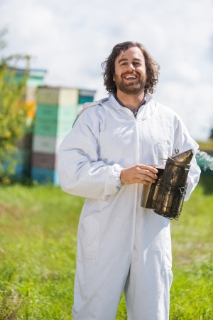 23727807 - portrait of happy male beekeeper holding smoker while standing at apiary